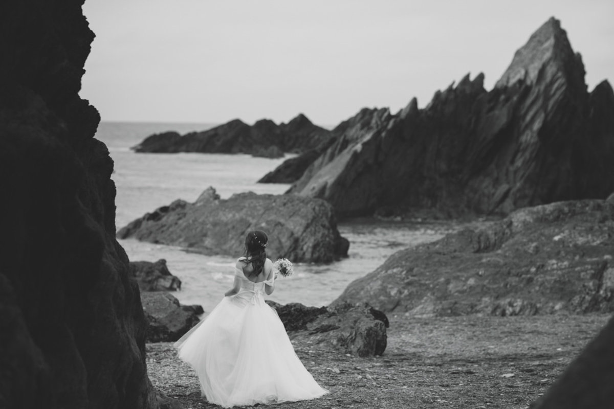 Black and White photo of Bride at Tunnels Beaches in Devon on the rocks