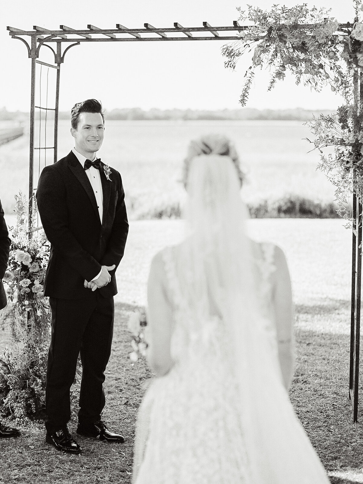 bride walking down aisle to groom in tuxedo at outdoor ceremony at Lowndes Grove Charleston wedding black and white