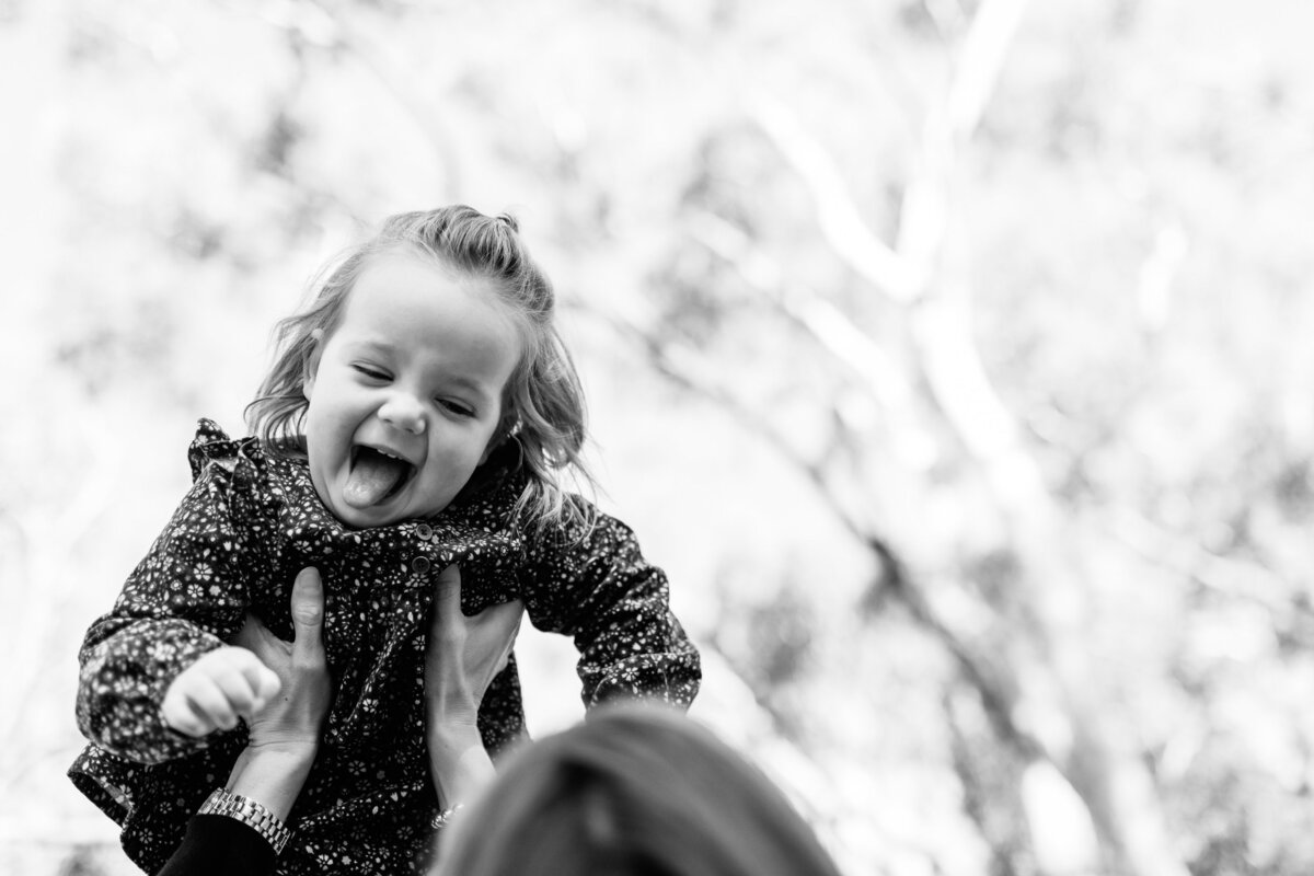 toddler laughing up in air outside Melbourne family photography And So I Don't Forget Photography