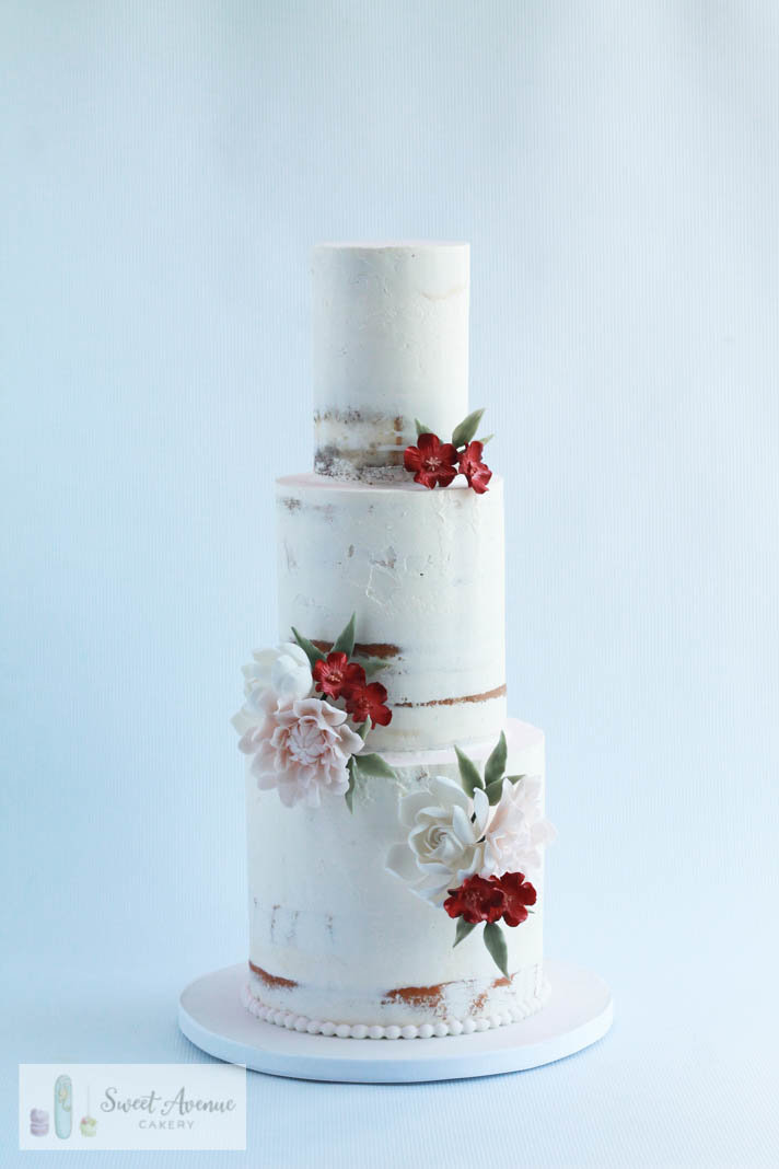semi naked rustic buttercream wedding cake with sugar flowers