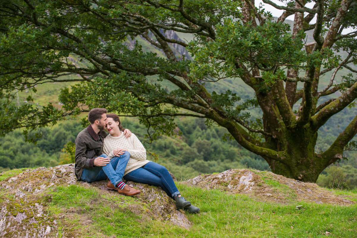 Young engaged couple in aran sweater and denim jeans kissing under a tree in a field
