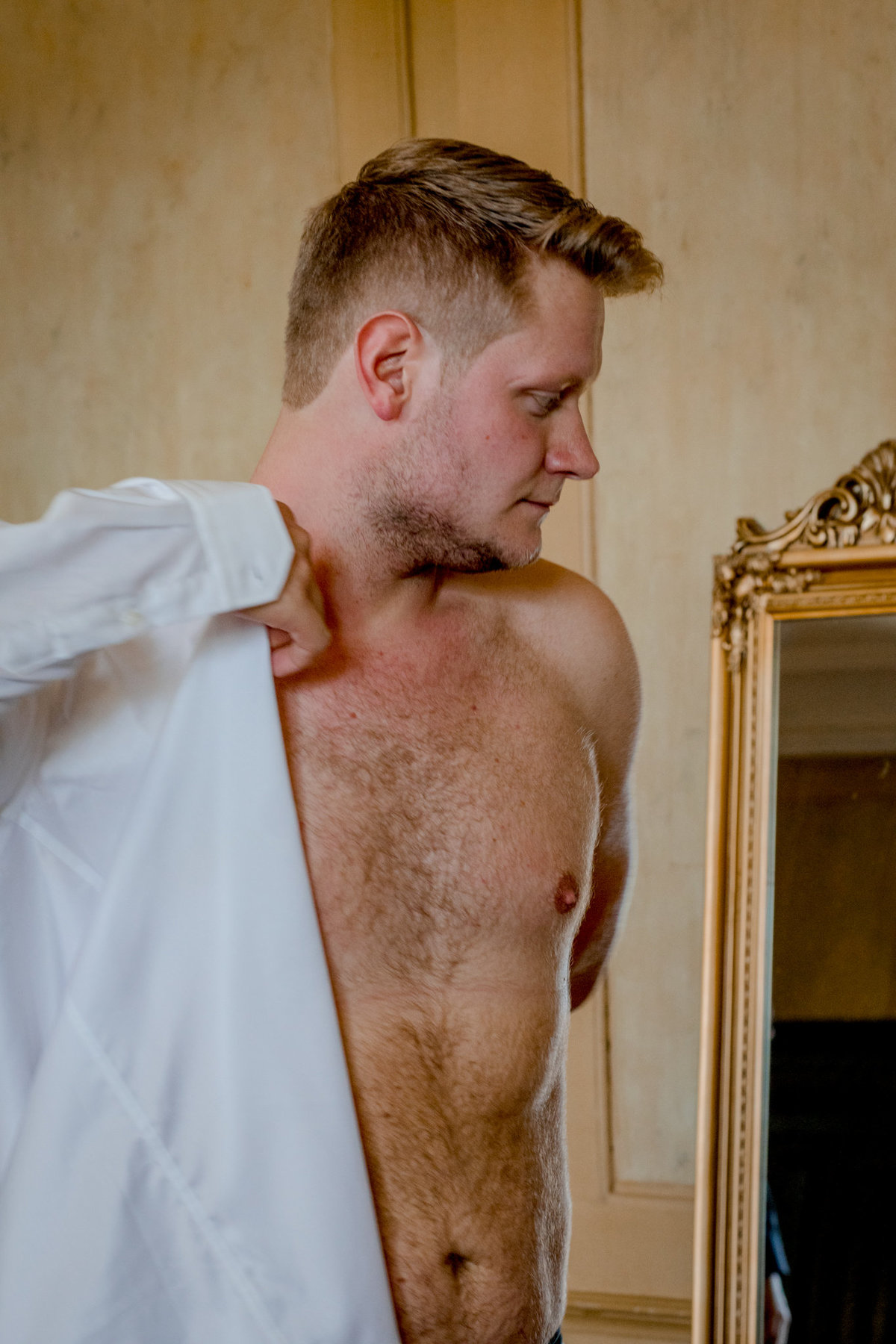 Groom getting ready and putting his white shirt on