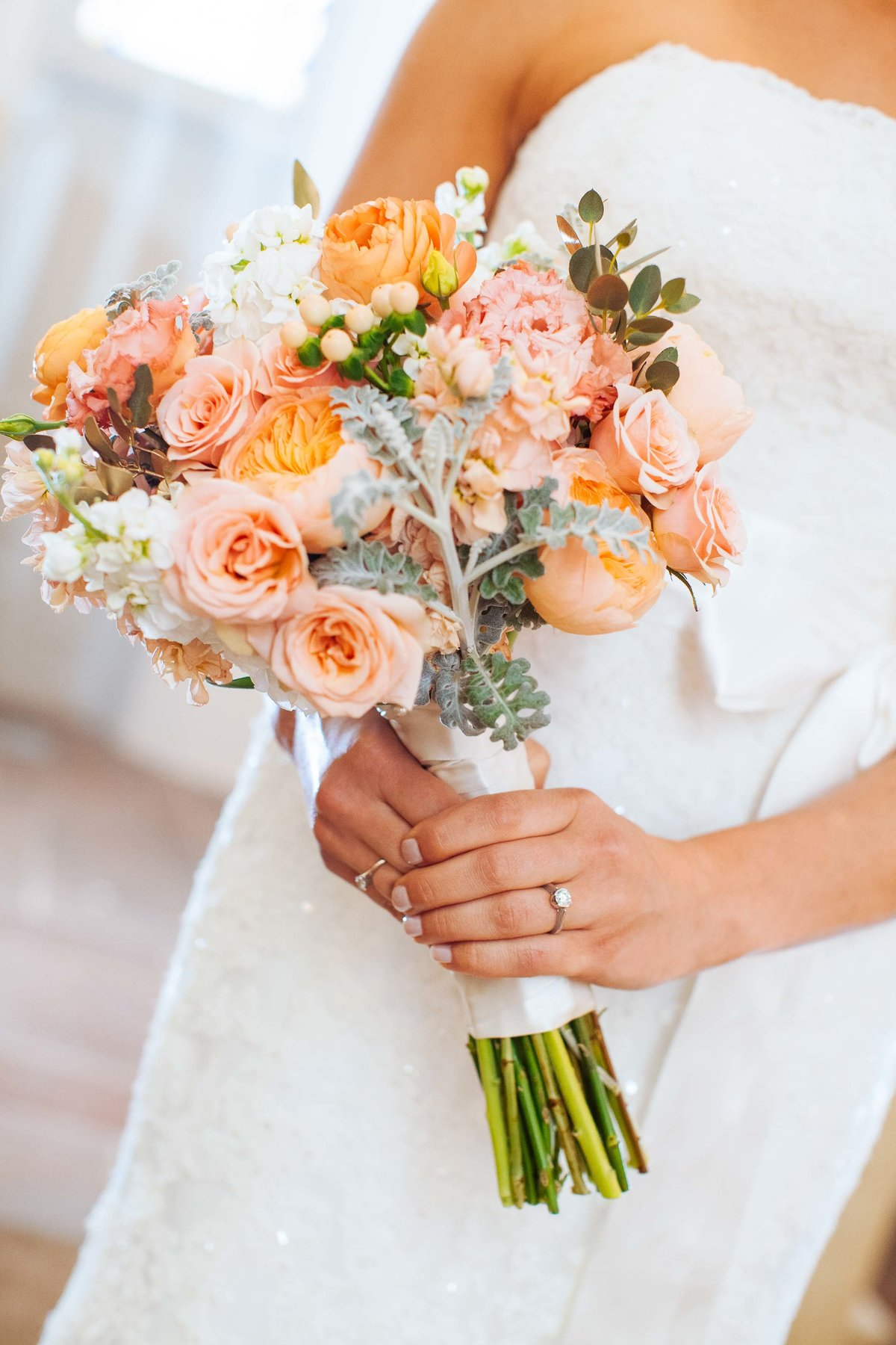 A bride holding her bouquet of flowers.