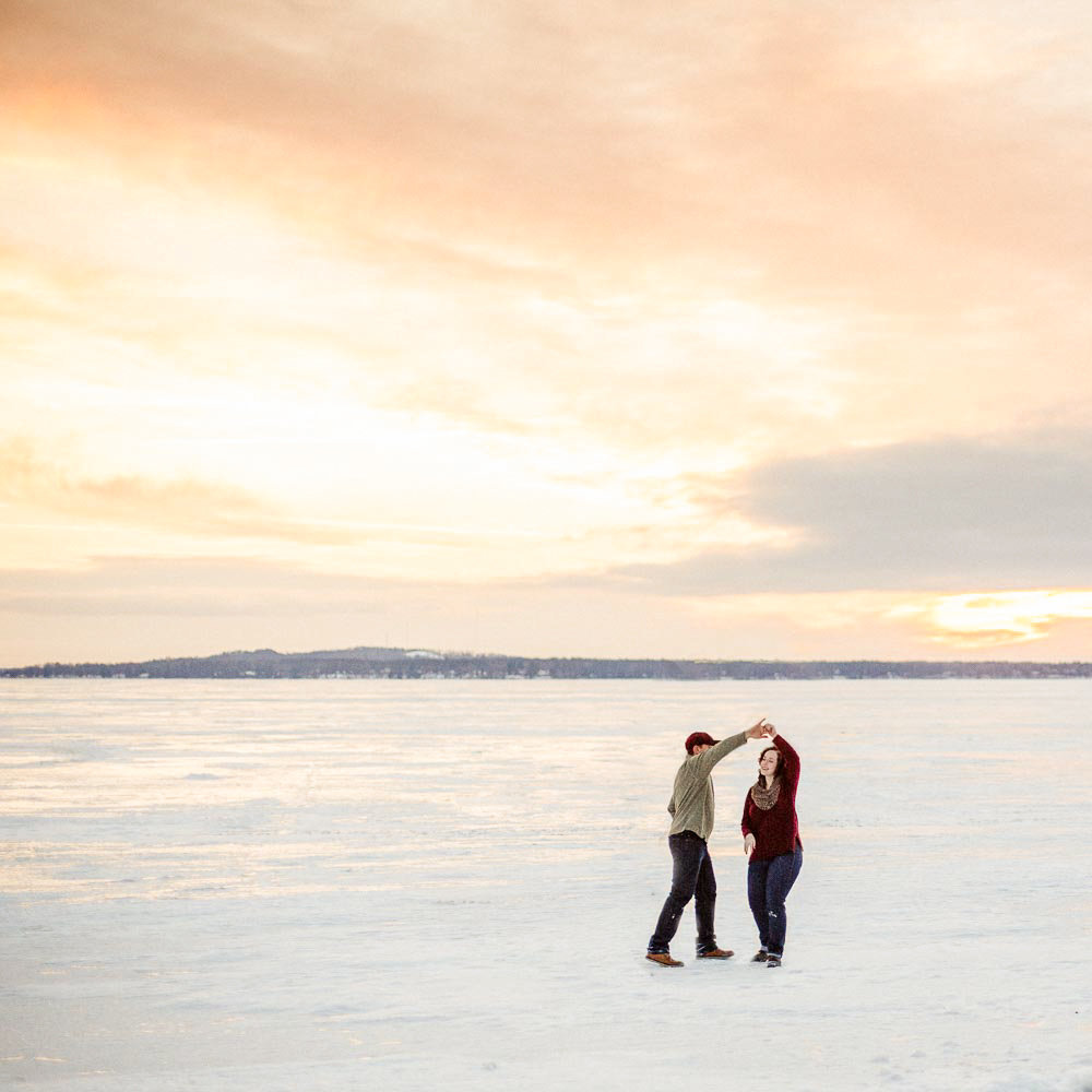 frozen gull lake in the winter couple dances over lice and sunset
