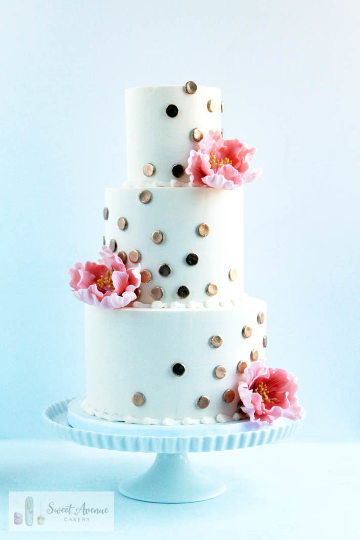 white wedding cake with gold polka dots and pink sugar peonies