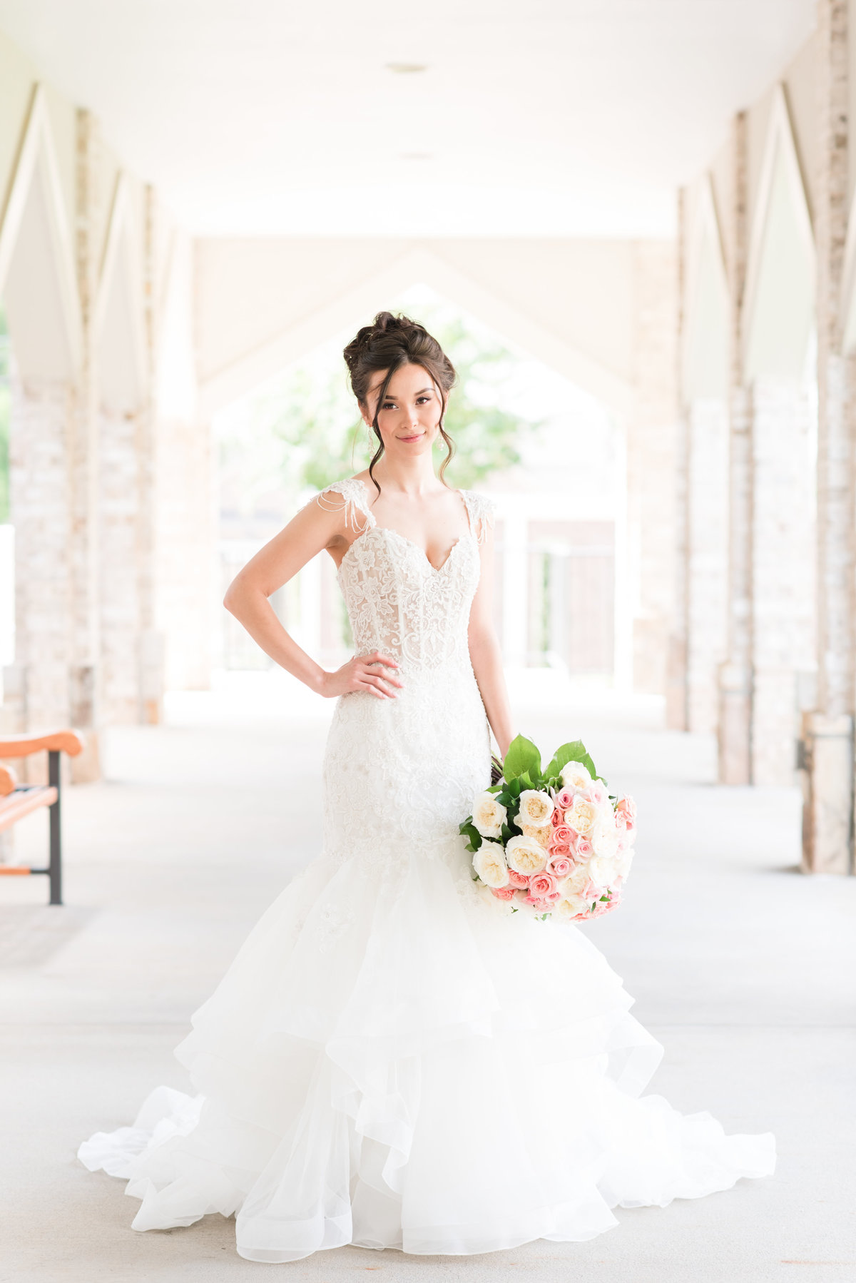 bride wearing a lace corset mermaid style wedding dress with a large pink and cream wedding bouquet surrounded by cream brick arches in Greensboro NC