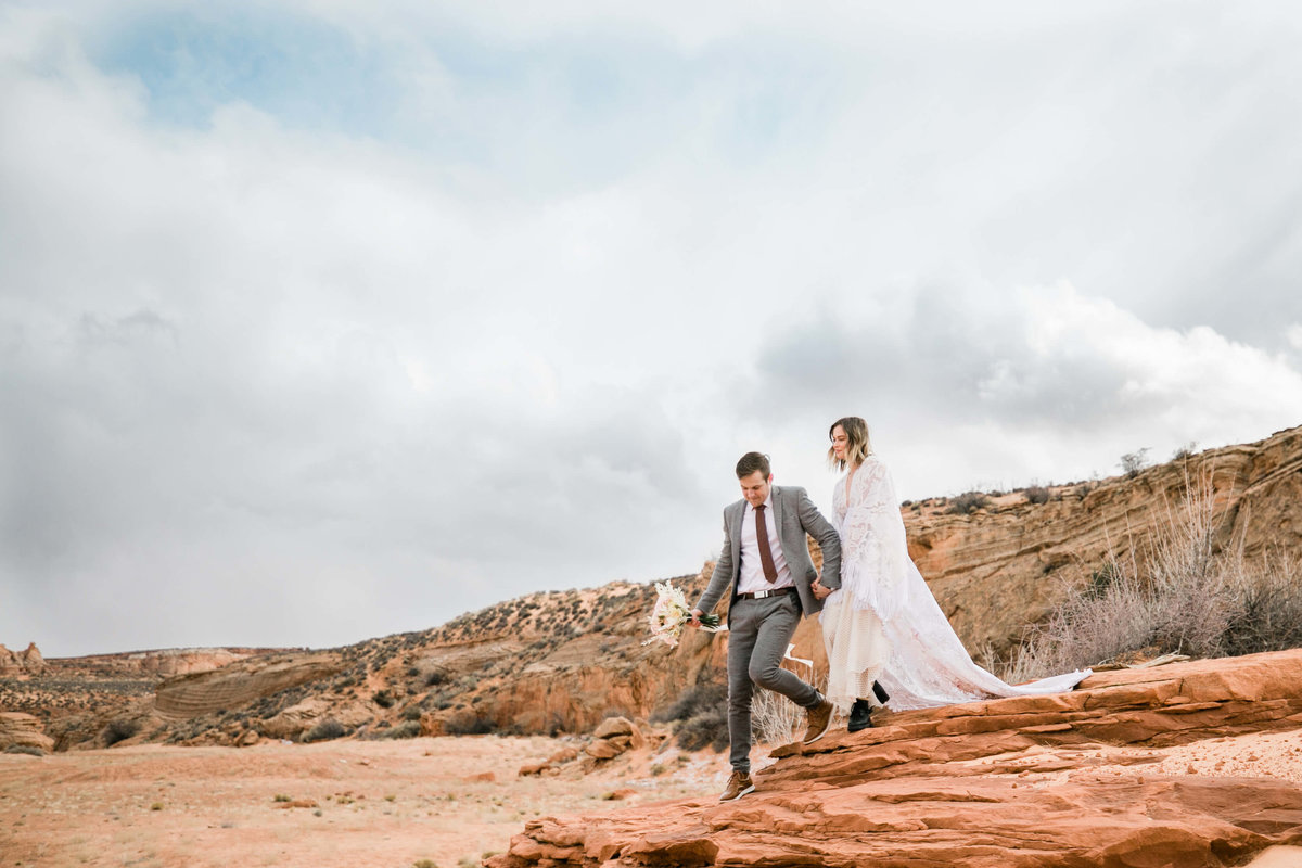 Holding his bride's hand, the groom leads the bride down a red rock during their arizona elopement