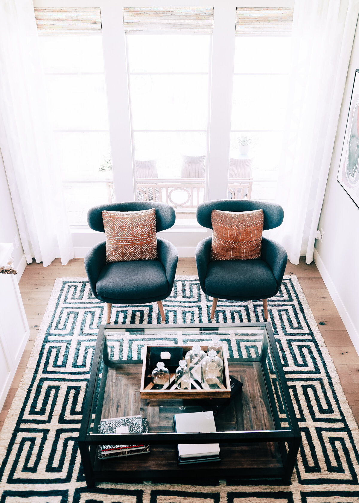 Two blue armchairs with red boho cushions with a monochrome pattered rug.