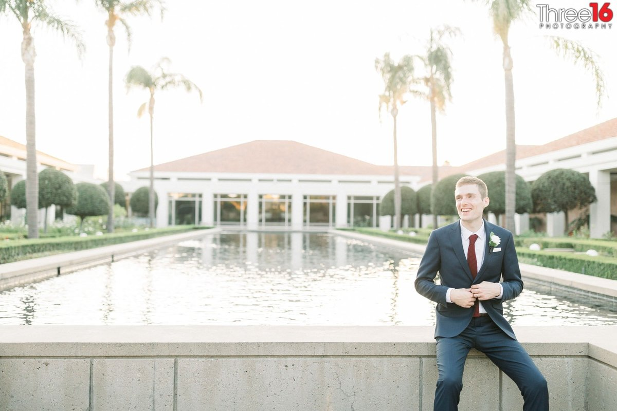Groom adjusts his coat while sitting on the reflecting pool wall at the Richard Nixon Library