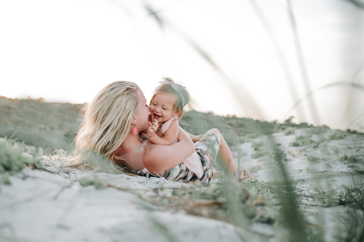 A photo of a mother laying in the sand with her daughter taken by Jacksonville Family Photographer
