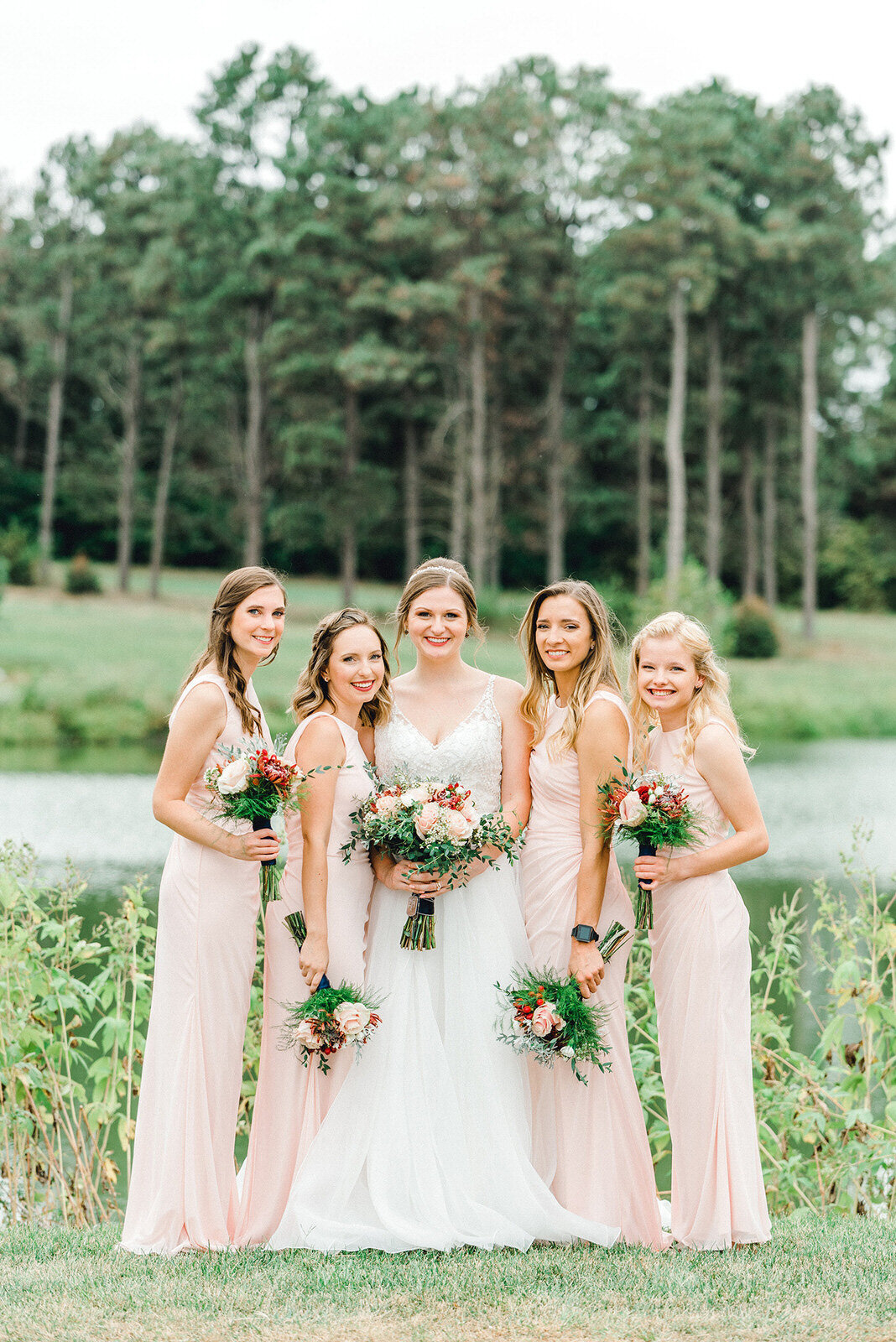 bridesmaids pose in front of lake at pioneers park