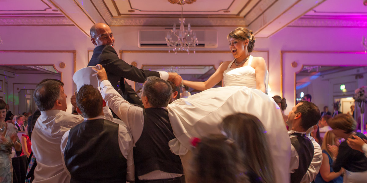 colourful reportage image of a bride and groom lifted high on chairs during wedding celebrations