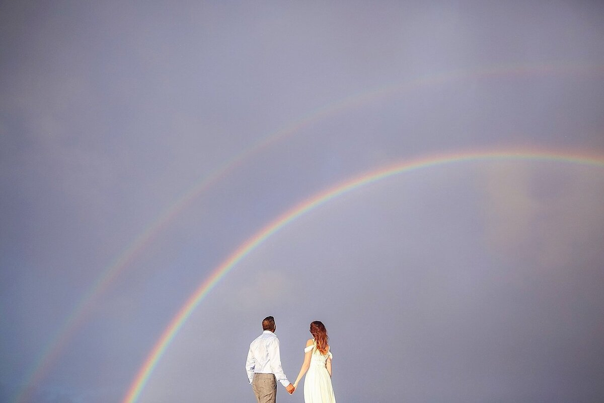 Bride and groom stand under a double rainbow on Maui after their wedding day
