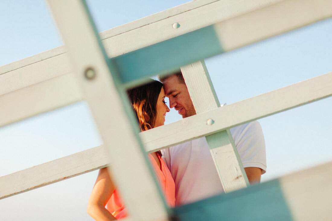 Couple embraces each other in front of a lifeguard tower in San Clemente, Ca.
