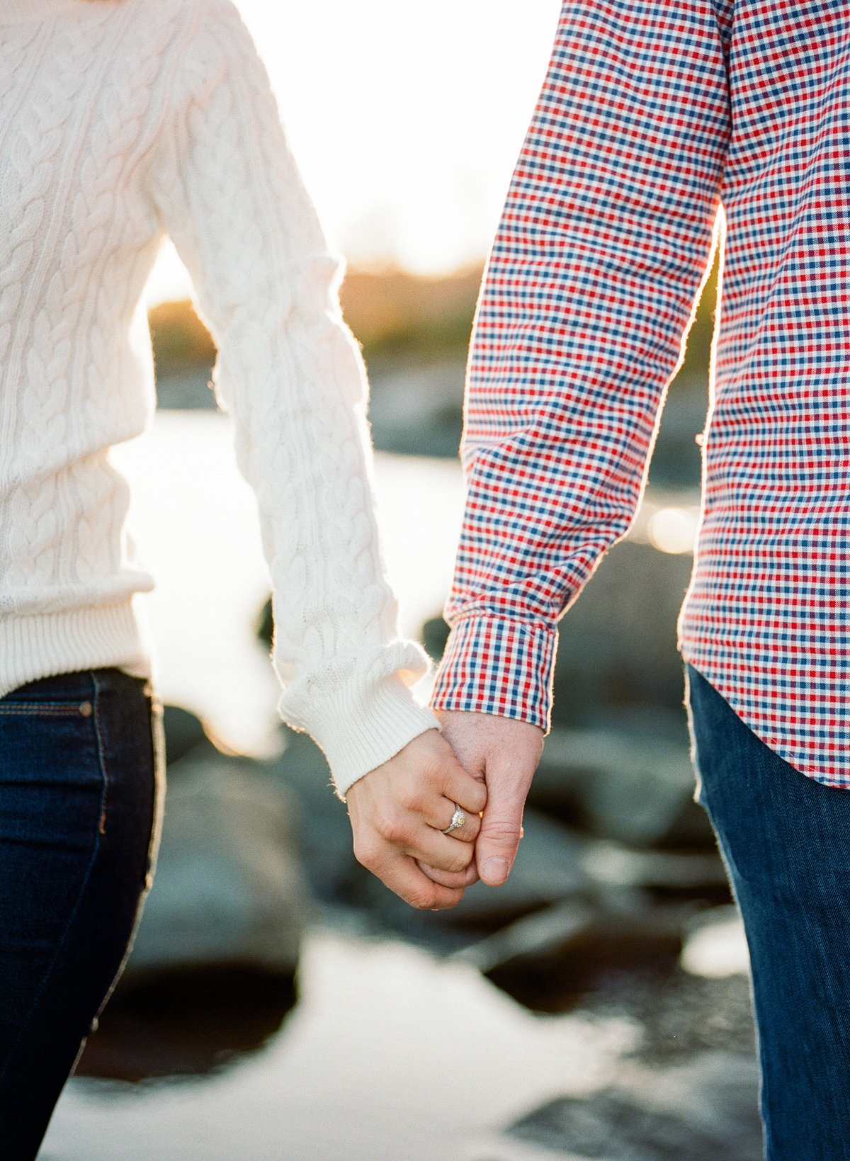 couple holds hands for engagement photography on north shore of minnesota