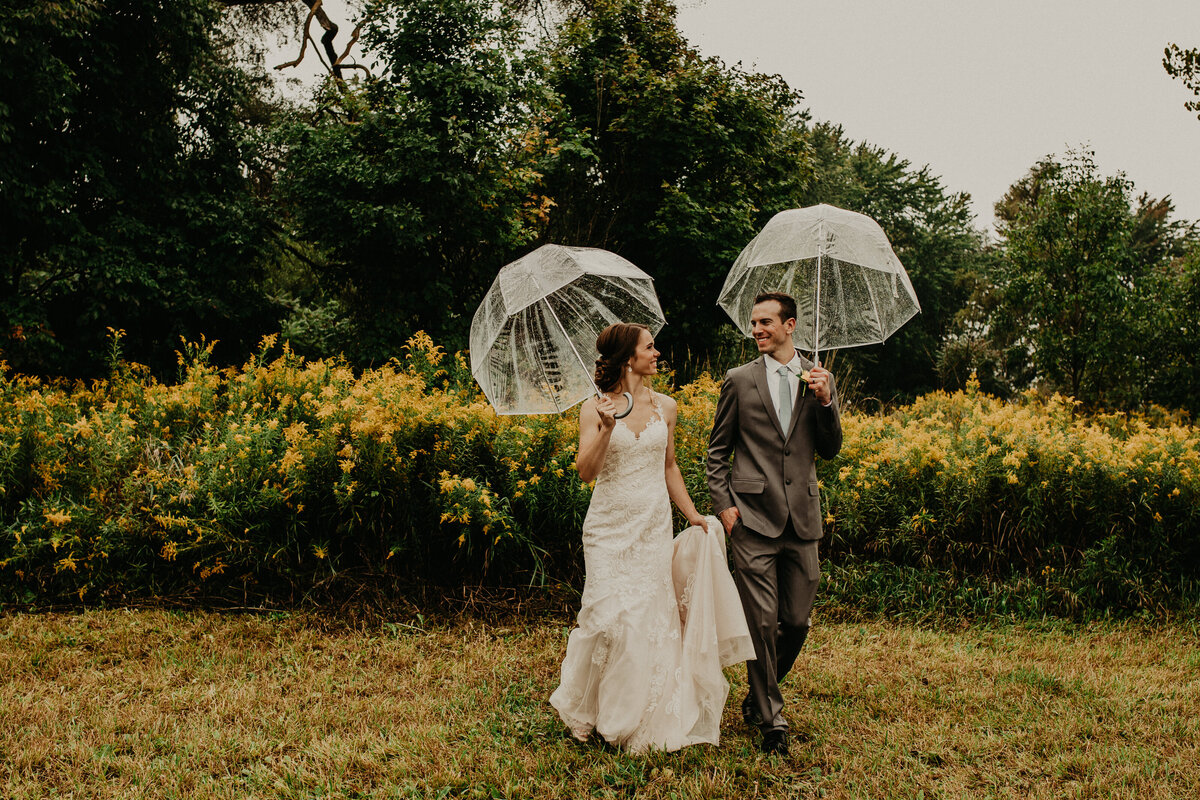 bride and groom walking with umbrellas in grass with wildflowers behind them