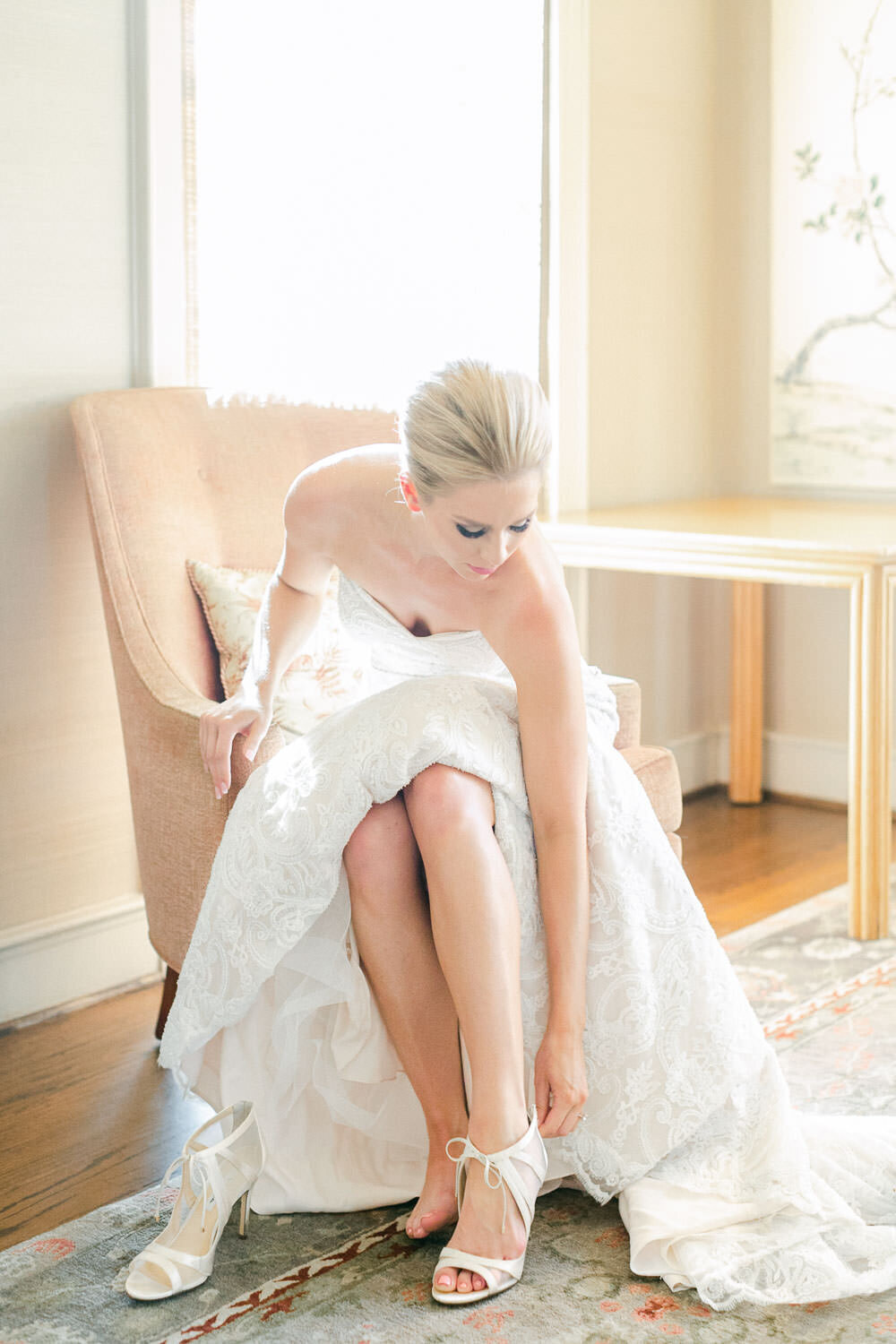 Bride sitting putting on white high heel shoes