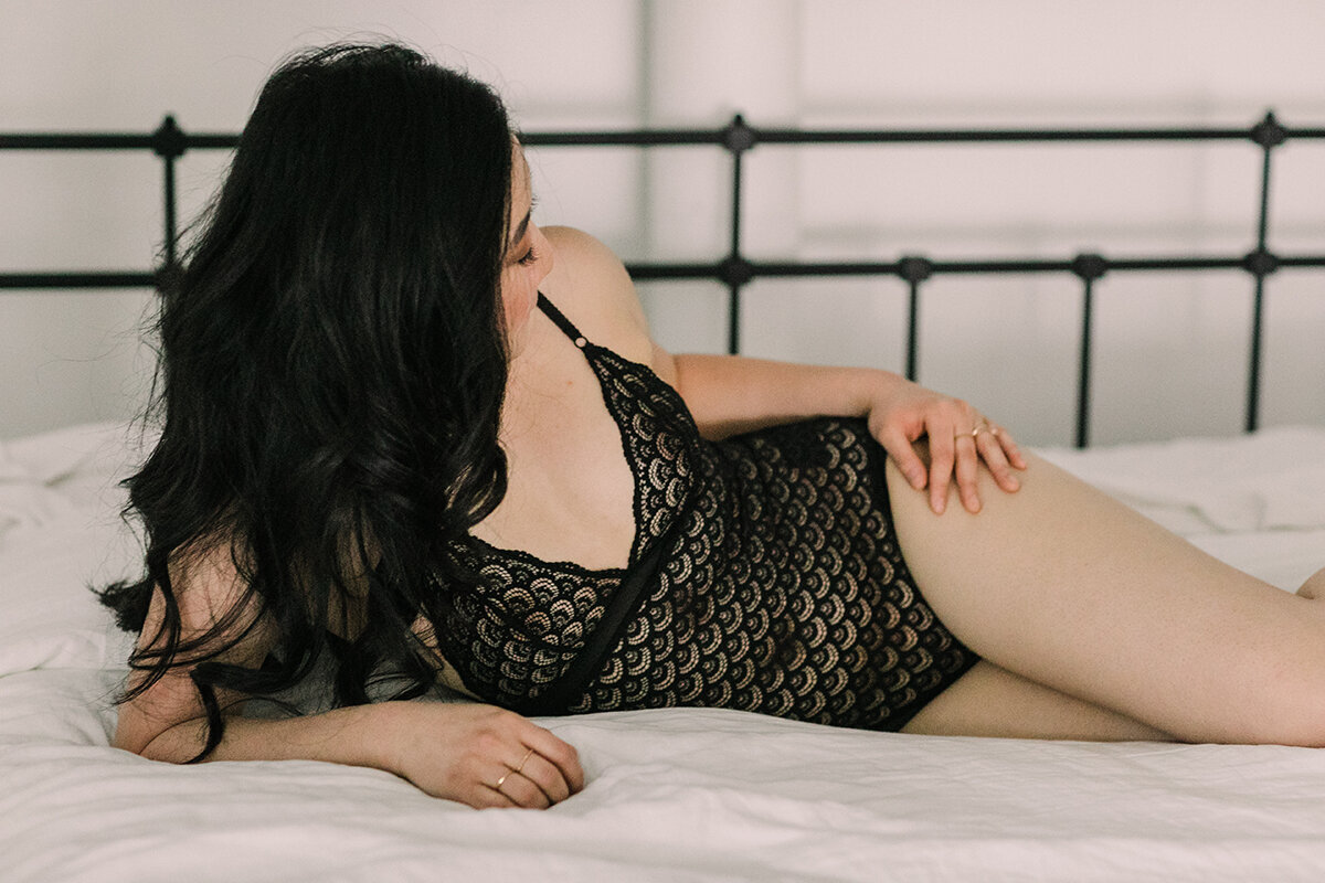 A woman lounging in bed while posing for a boudoir photo.