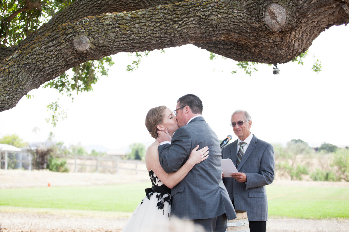 bride and groom have first kiss at their rustic inspired santa ynez wedding