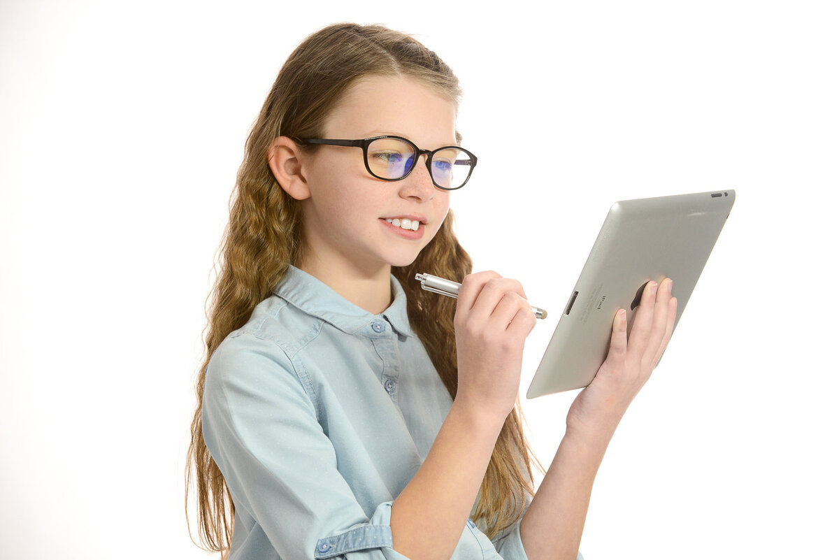Girl wearing UV blocking glasses looking at an ipad on a white background