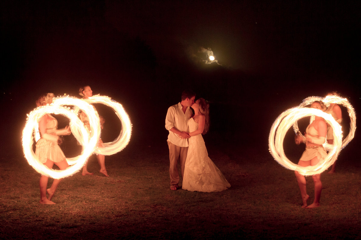 Kissing couple with fire dancers at Kauai wedding