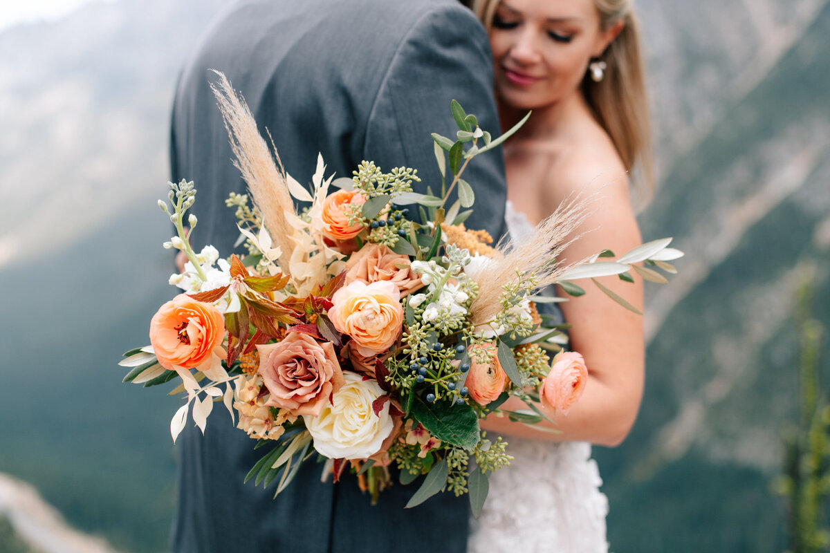 Bride holding colorful fall bouquet by Twisted Willow Floral during North Cascades elopement