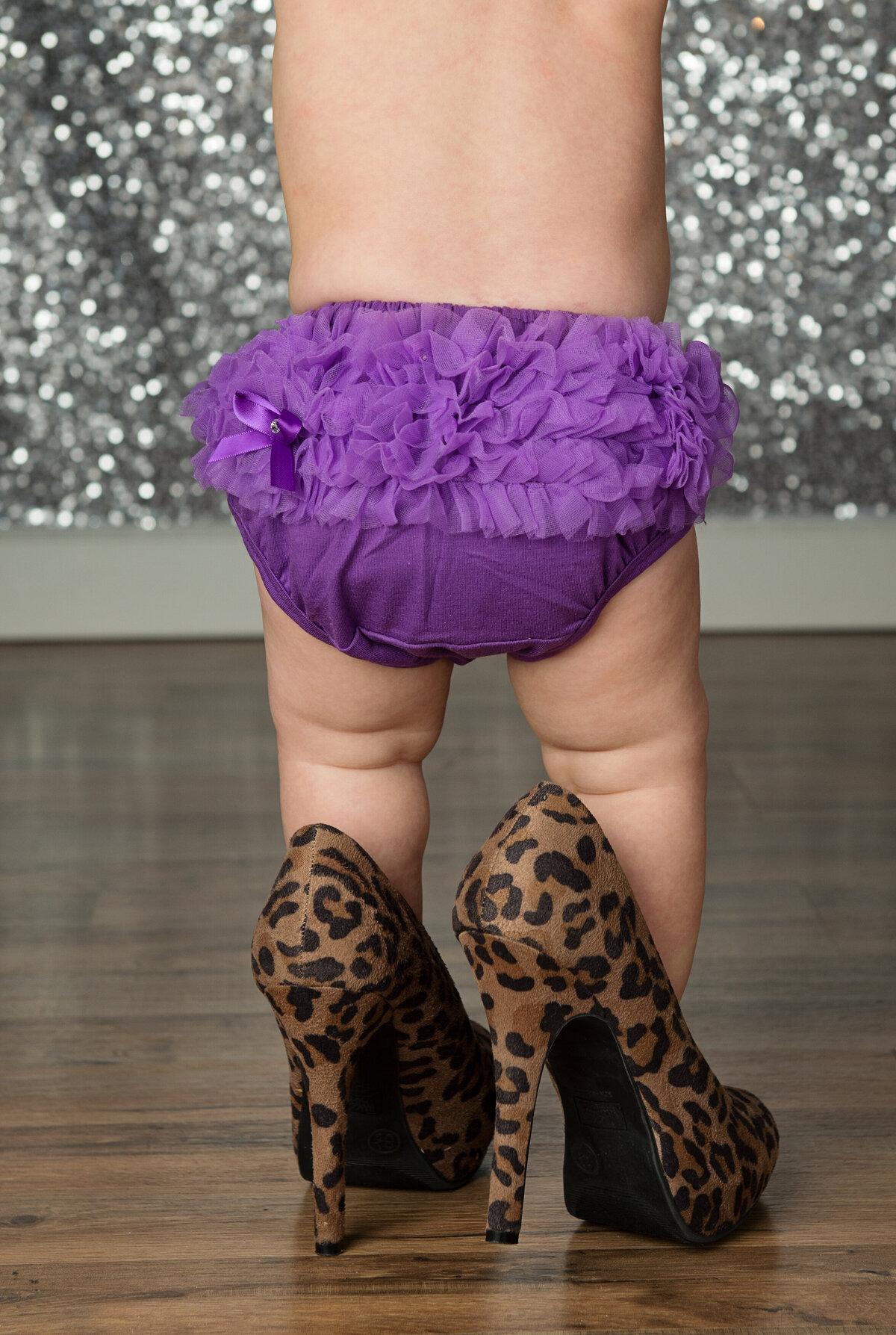 baby in purple diaper cover with high heels