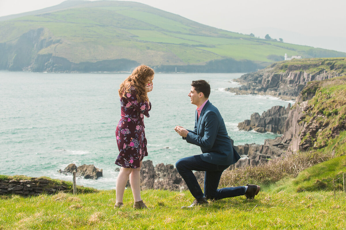 Young man going down on one knee to surprised girlfriend with red hair on a cliff overlooking the sea
