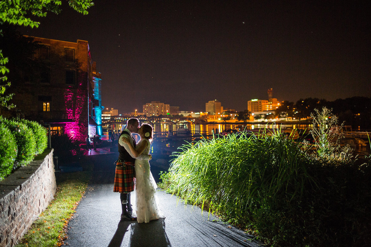 groom wearing kilt kissing bride at nighttime at prairie brewing company in rockford illinois