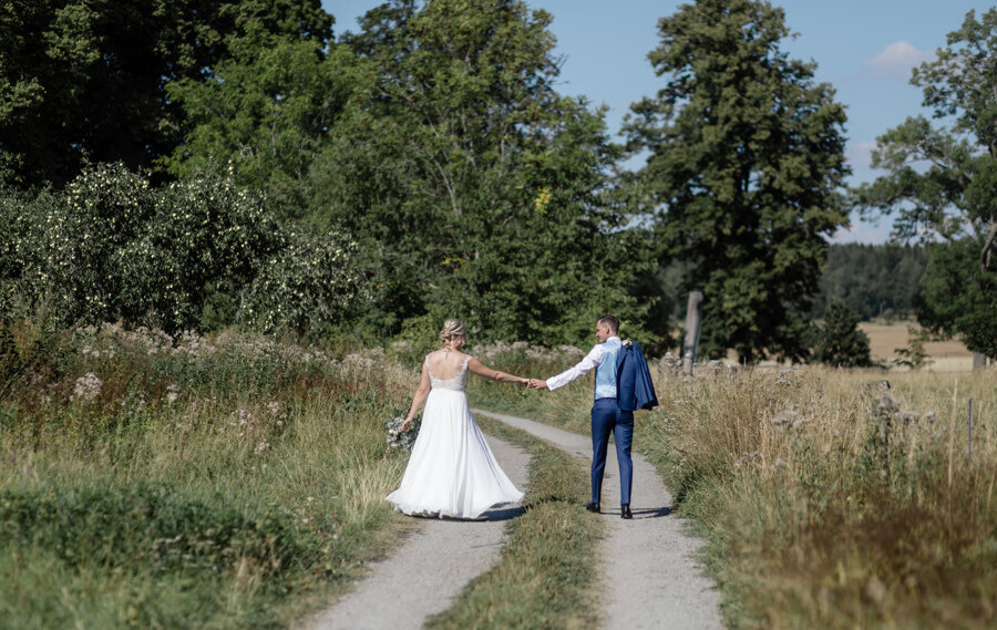 Newlyweds strolling on a path in nature outdoors