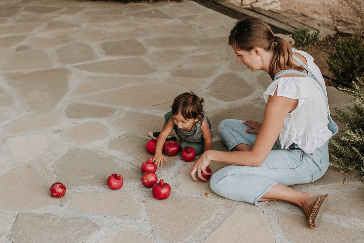 mother son playing with pomegranates
