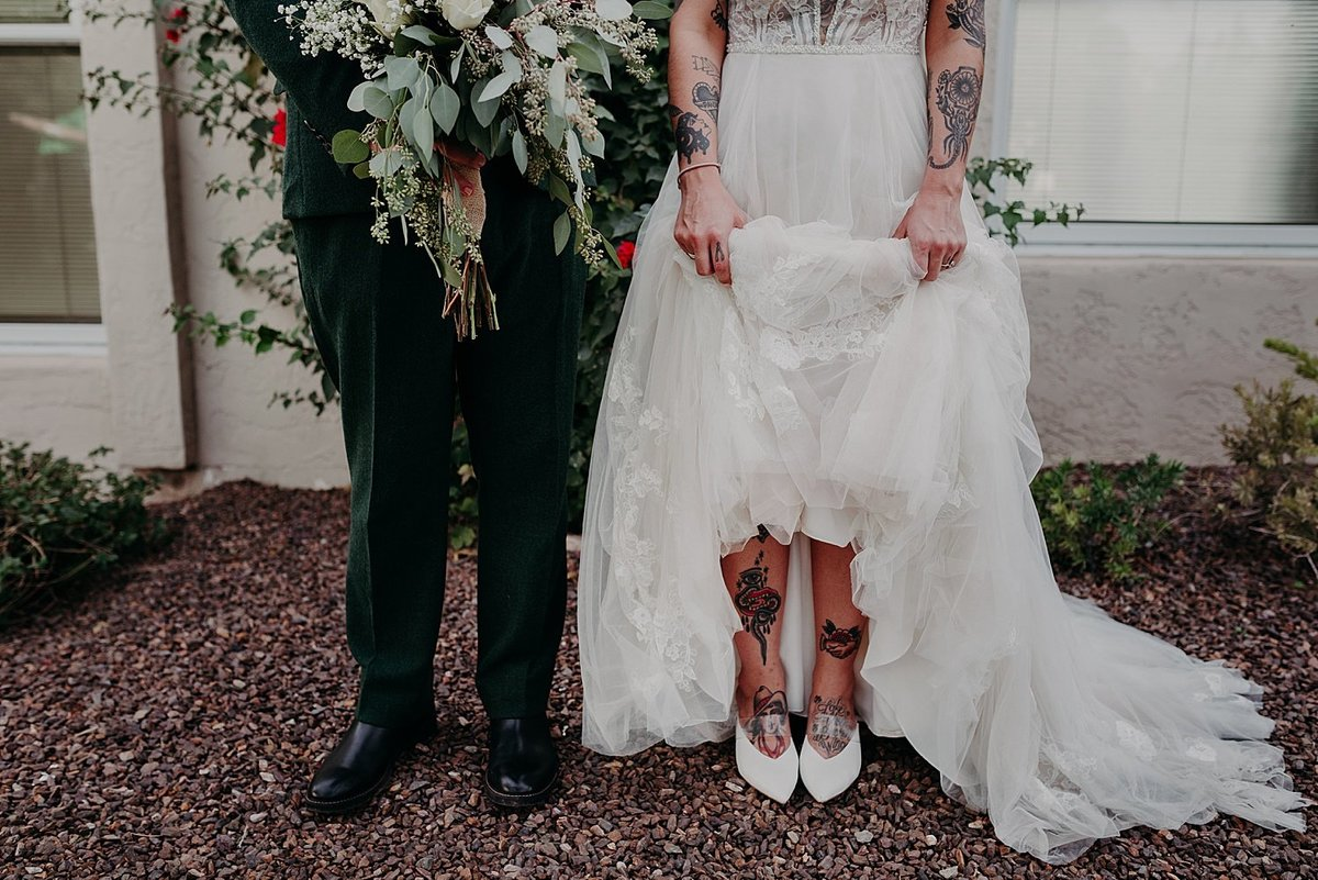 Bride and groom stand side by side as the bride lifts her dress to reveal her tattooed shins and feet