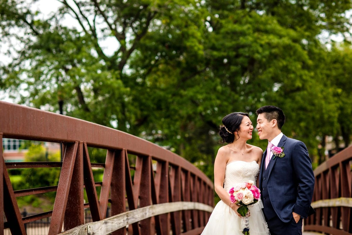A couple laughs together on a bridge before their wedding.