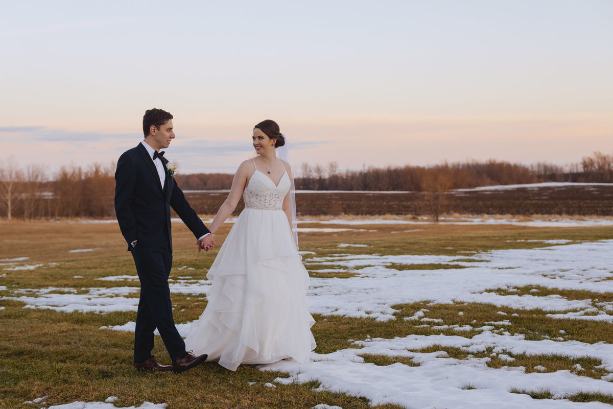 bride and groom  walking across a snow covered field at sunset
