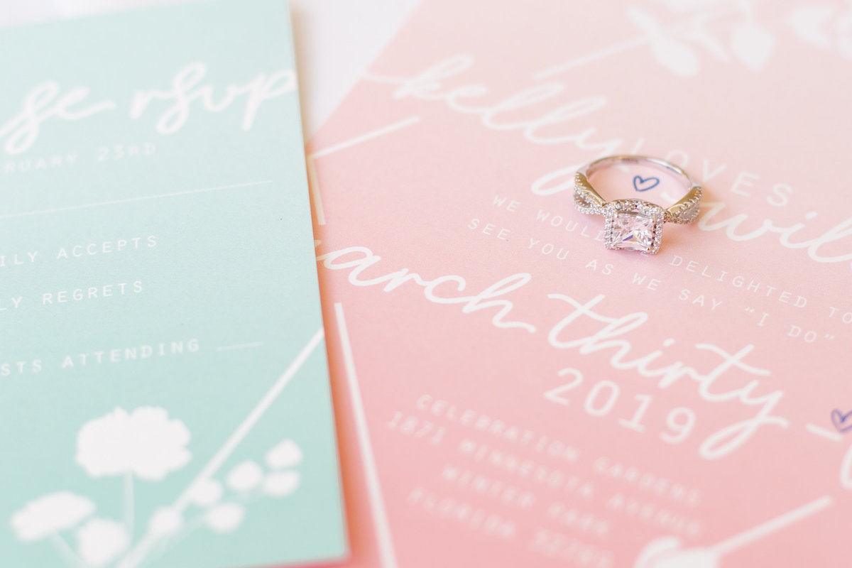 Spring colored wedding invitation with sweet font and heart with engagement ring being featured around the heart dotting the i