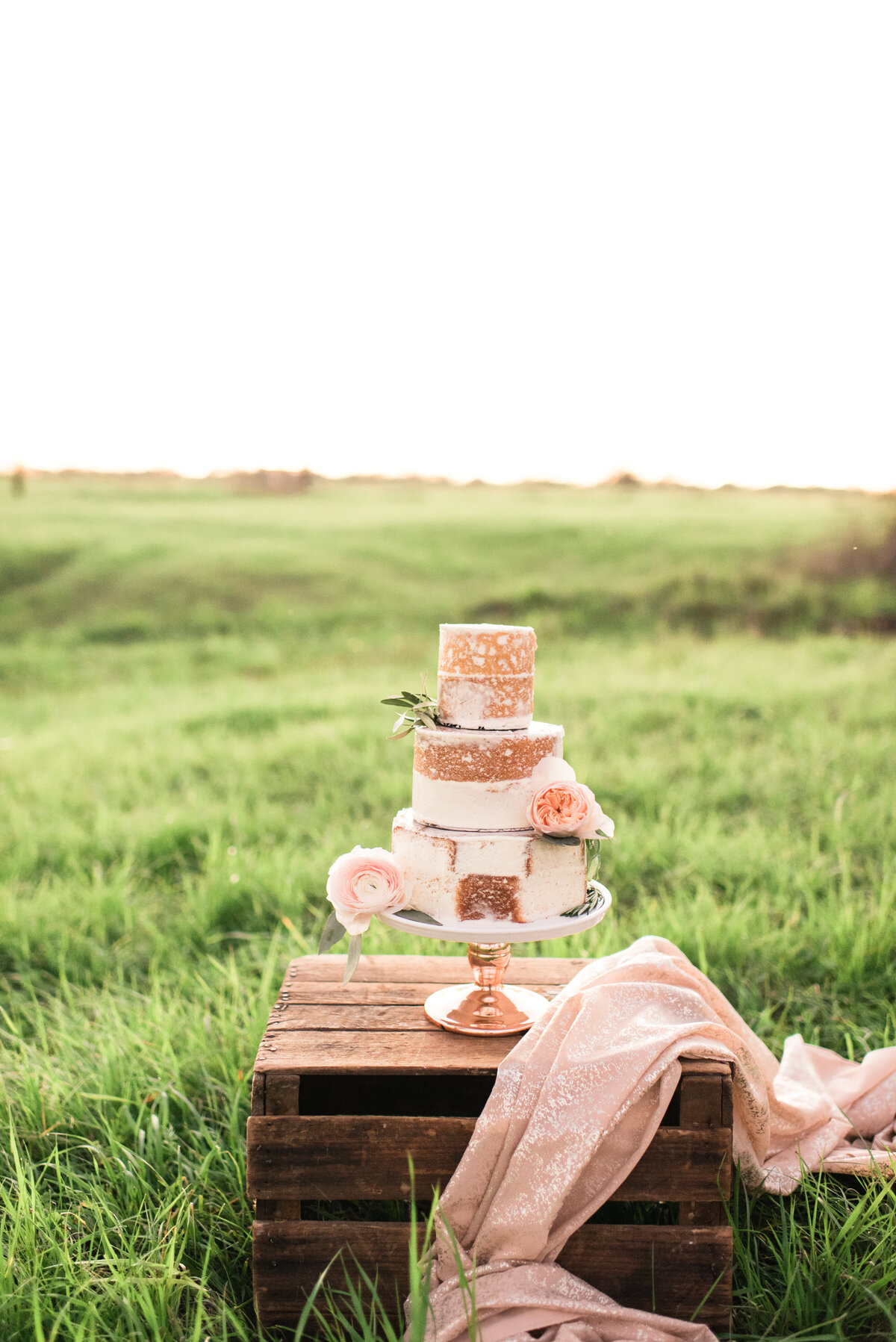 A gorgeous naked pink wedding cake photographed in a lush green field