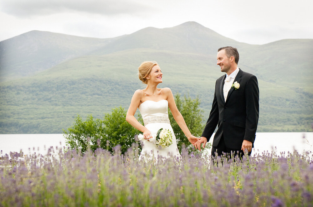 red haired bride wearing an a-line dress, holding hands with her groom in a black suit and white tie surrounded by lavender flowers standing in front of a lake in Killarney