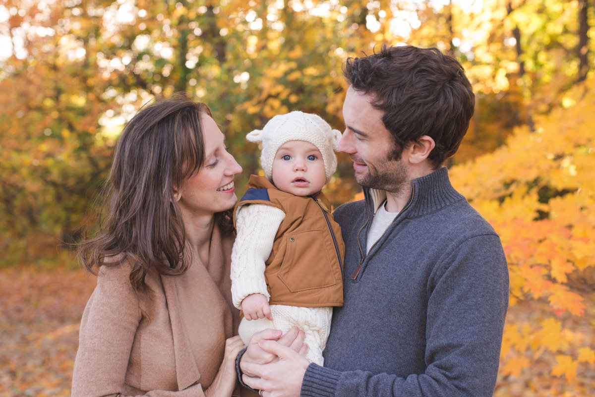 Family of three smiling standing in the autumn leaves