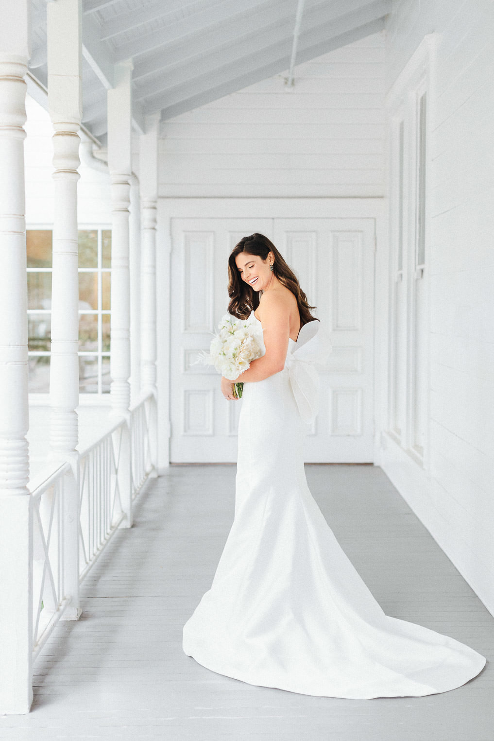 bride in strapless wedding dress with bow standing on white porch with bouquet at Mattie's Austin