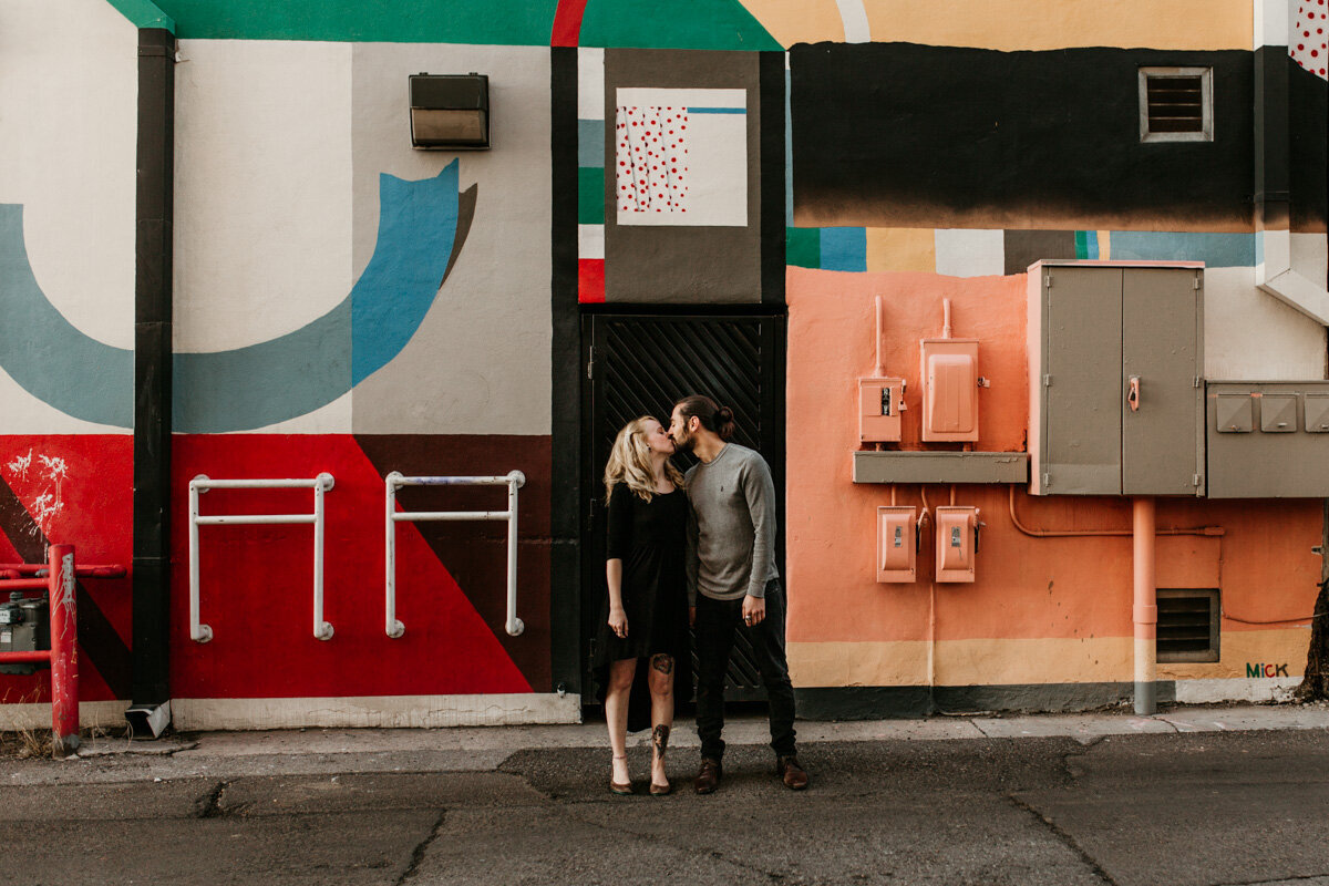 couple kissing in front of an art wall downtown Albuquerque
