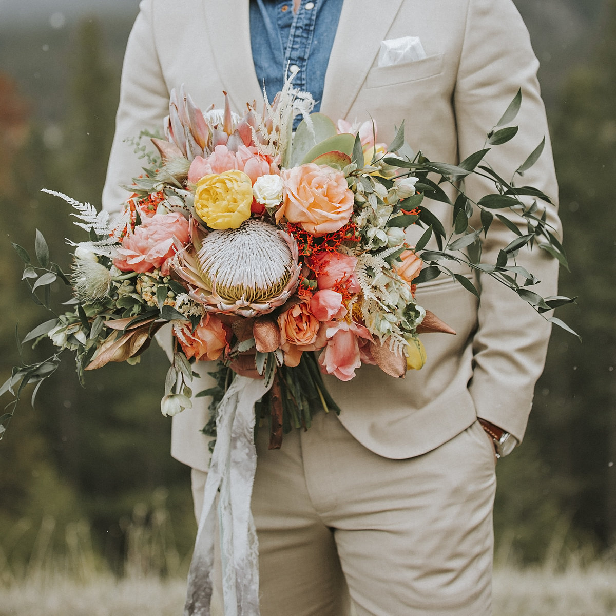 Groom standing on top of mountain holding large floral bouquet from Fabloomosity