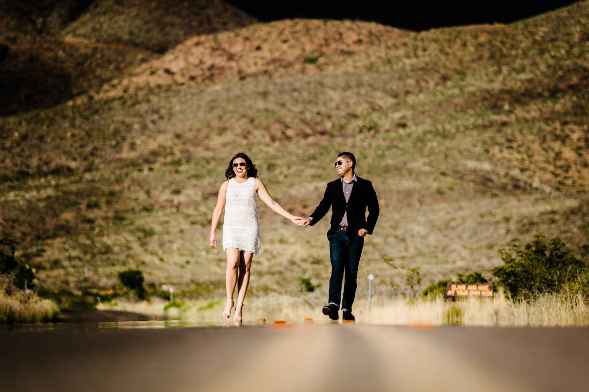 couple smiling during their el paso engagement session in front of franklin mountains