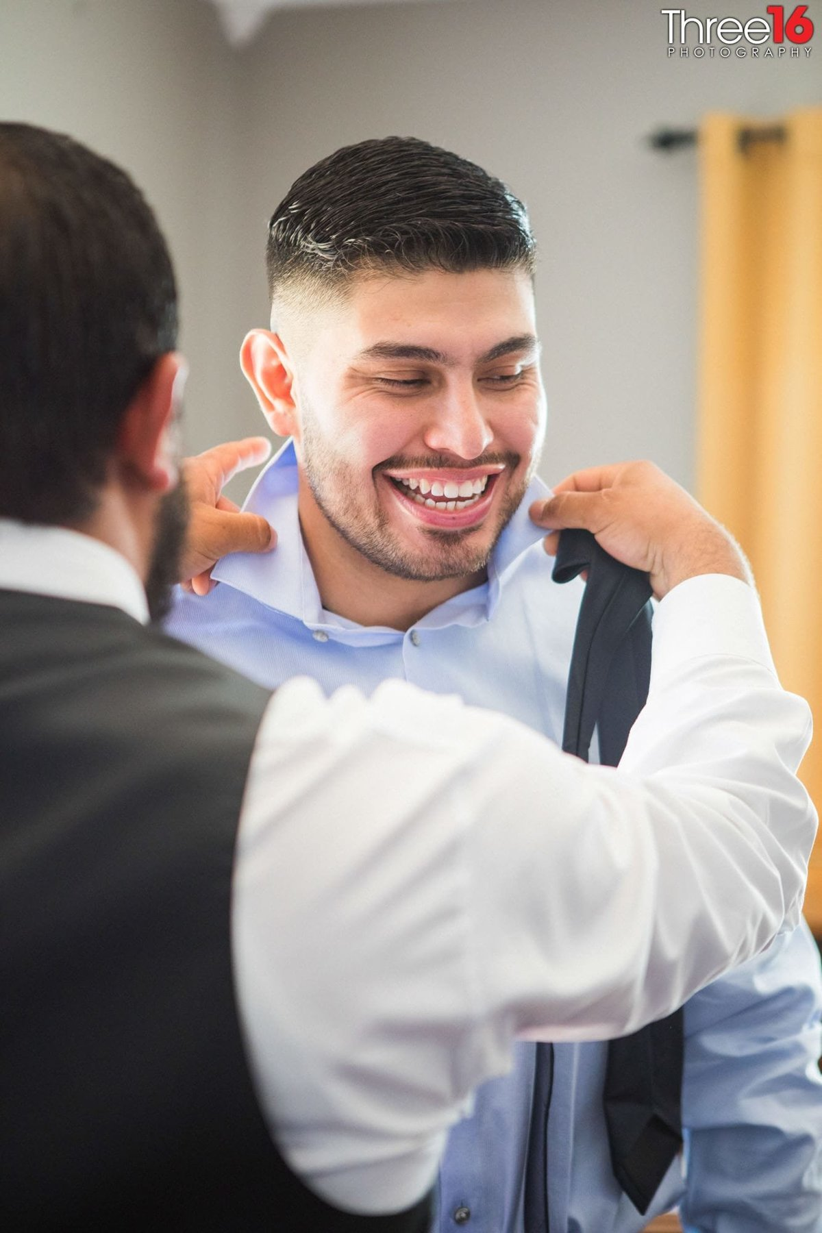 Groom getting help with his tie while getting ready for the wedding