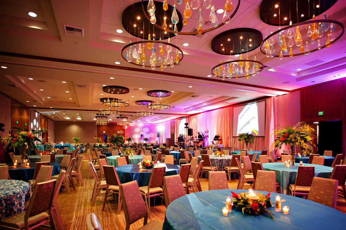 large company party with a tropical theme with turqoise linens, and tropical centerpieces