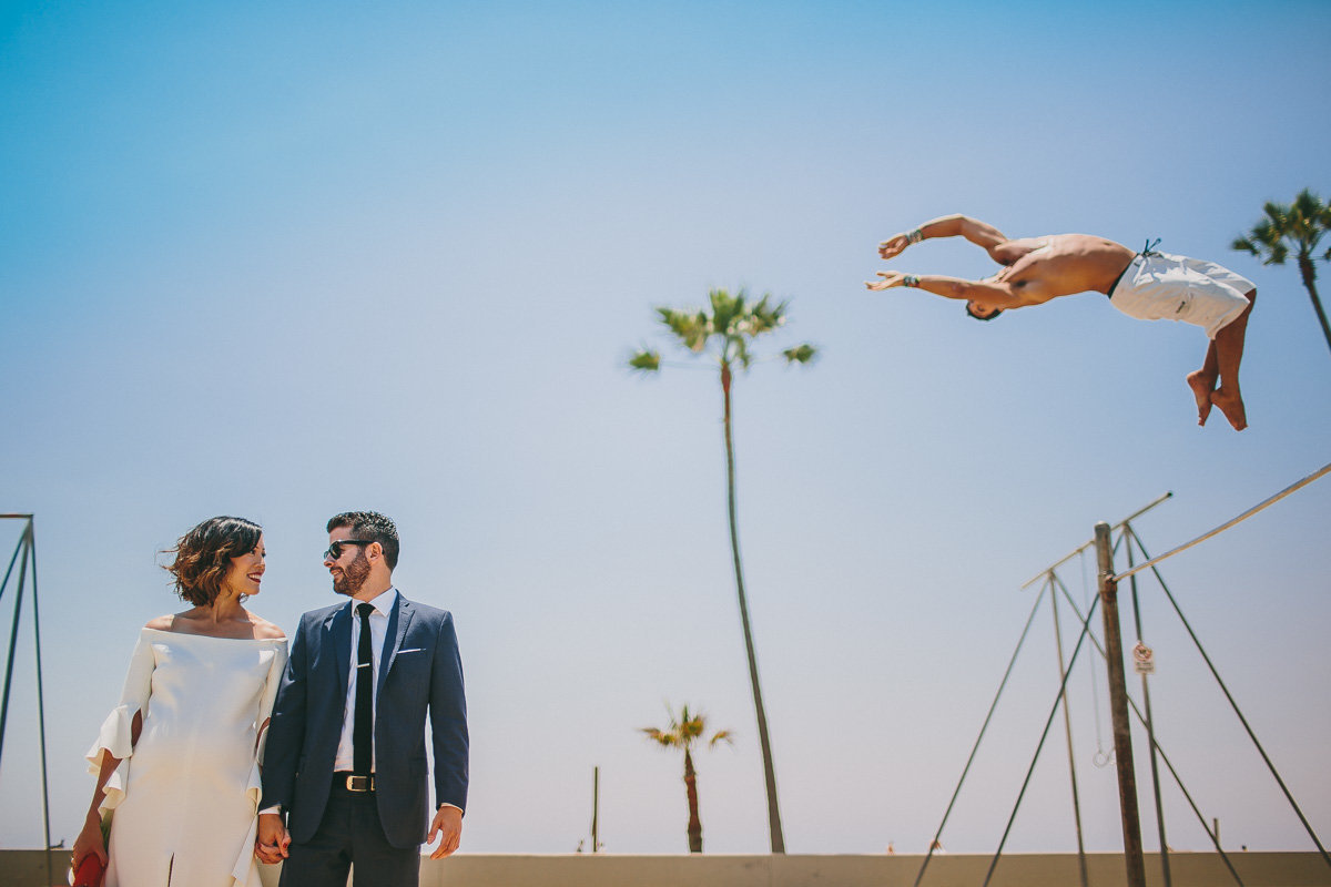 Bride & Groom hold hands as Venice Beach acrobat flips behind them.