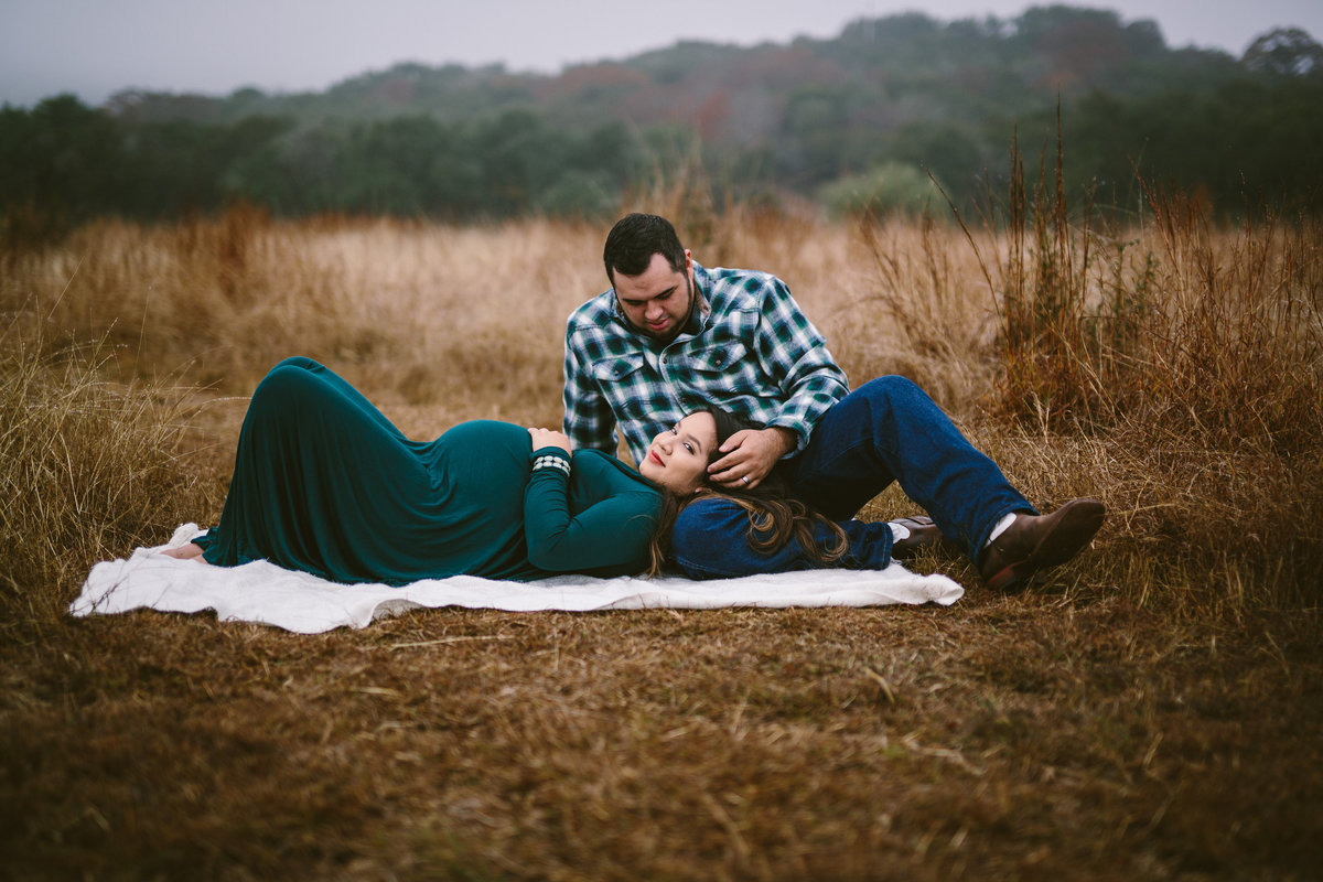 couple pregnant laying in open field in Texas hill country for their maternity session in Boerne