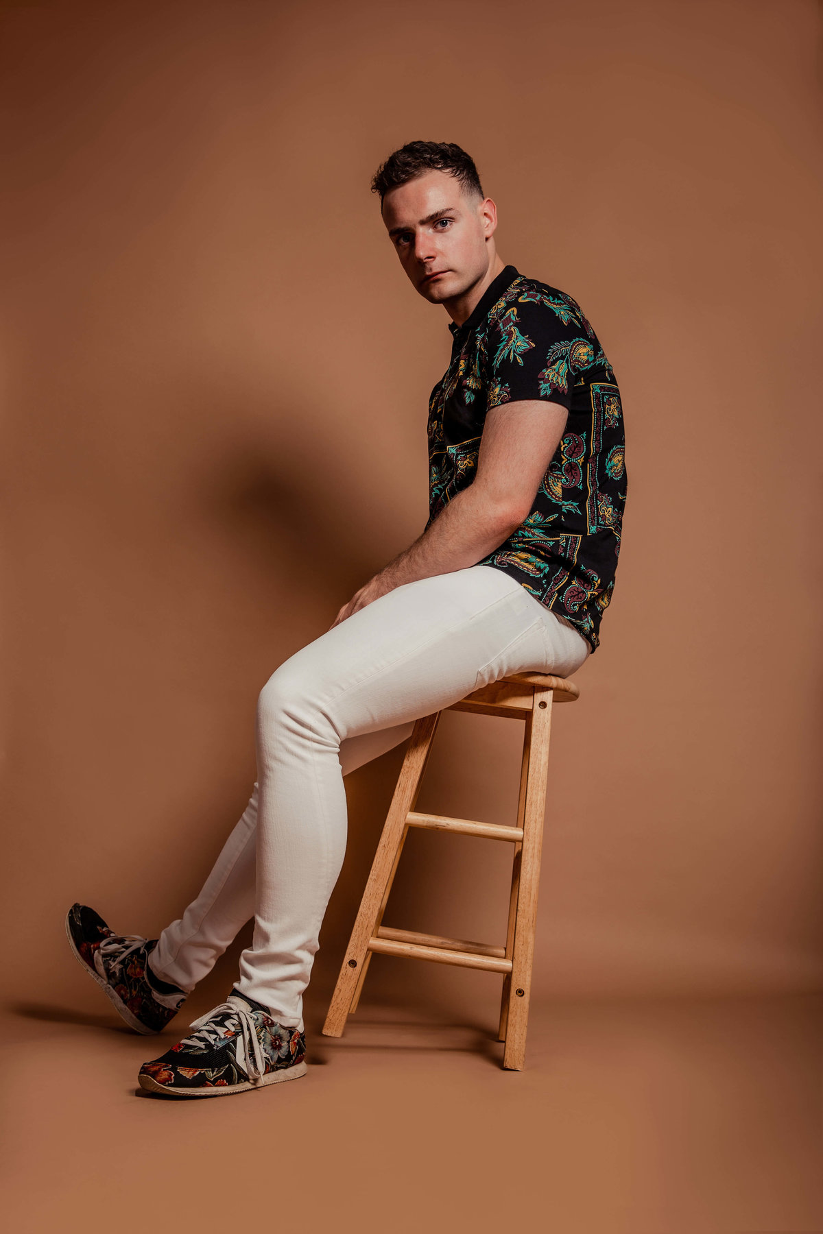 Connor sat leaning back on a stool against a tan background.