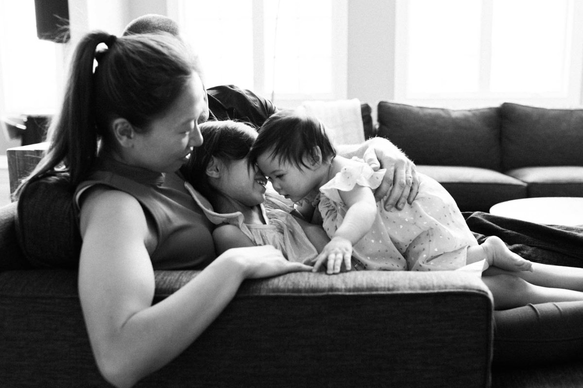 Family of four playing on couch during candid lifestyle family session