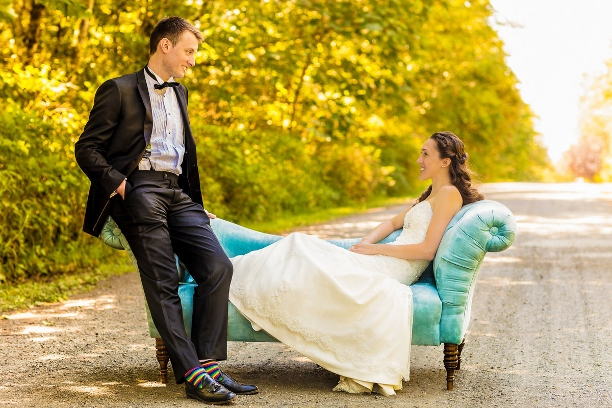 Outdoor wedding bride and groom sitting on a sofa on a dirt road