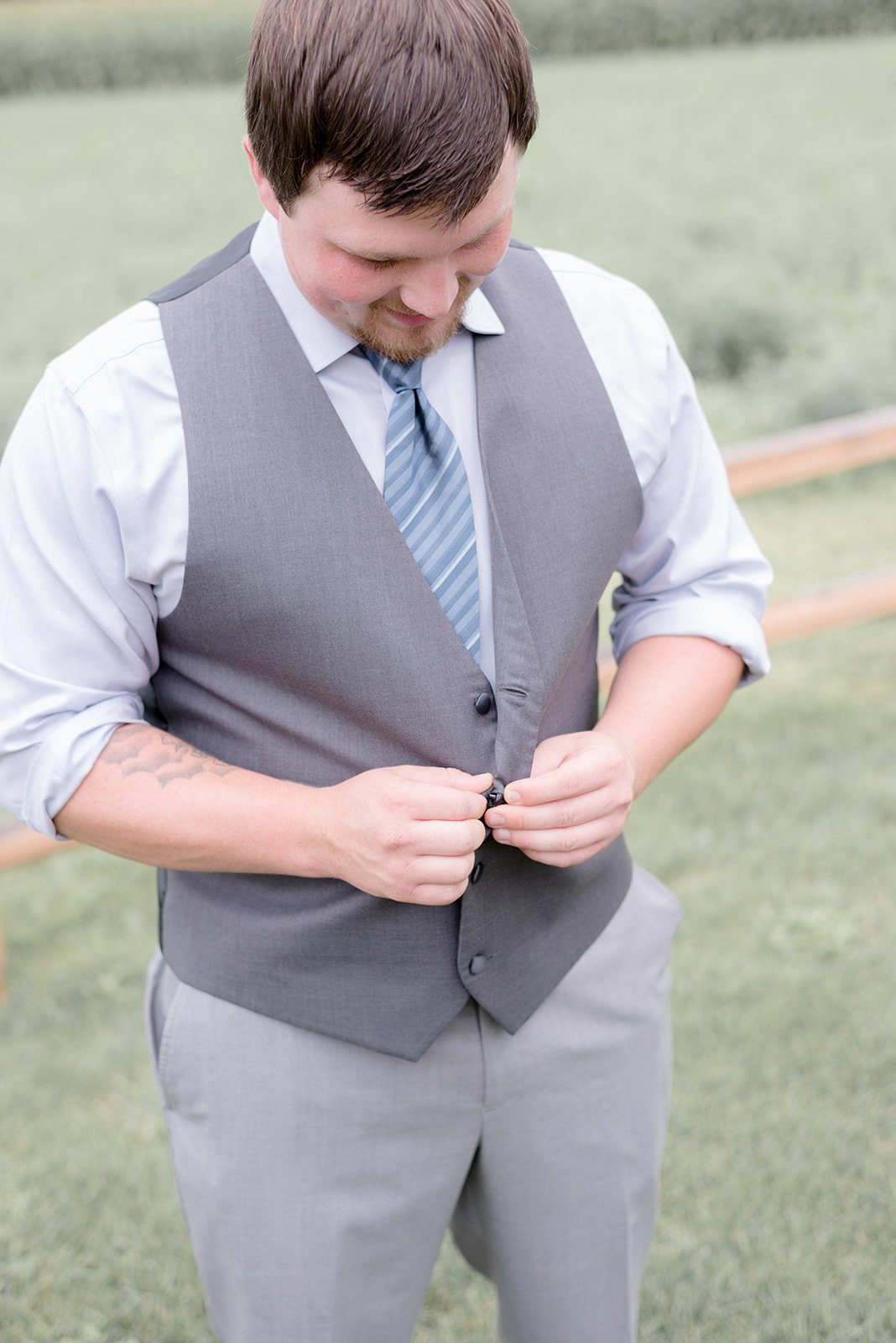Groom buttoning up his vest in Prescott Wisconsin
